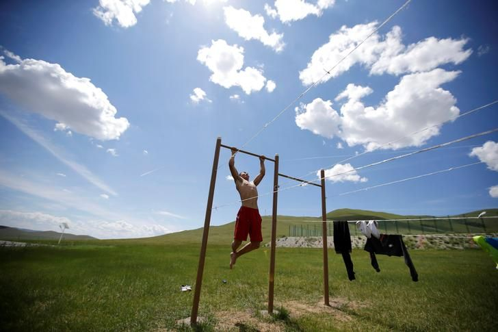OLYMPICS-RIO/WRESTLING-MONGOLIA A training partner of Mongolia's Olympic wrestler team does pull-ups after a daily training session outside the Mongolia Women's National Wrestling Team training centre in Bayanzurkh district of Ulaanbaatar, Mongolia.  REUTERS/Jason Lee