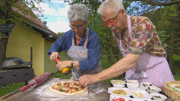 Martina und Moritz belegen eine Pizza am Grill | Bildquelle: wdr: Pizza selbst gemacht - Der Belag
