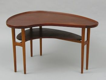 """A kidney-shaped teak wood table designed by Arne Vodder, with double tripod legs and a small inner shelf, branded underneath """"Bovirke Made In Denmark"""", with stapled tag """"by Arne Vodder"""", measuring approx. 22""""H x 37-1/2""""W x 38""""D-24-1/2""""D."""