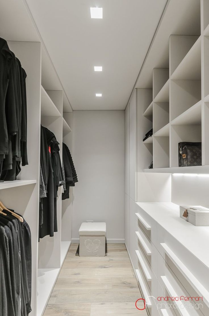 Narrow walk in closet with lots of built in shelves...of course the