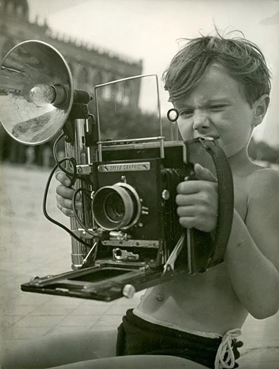 This is a speed graphic press camera the boy is helmut newton he became one of worlds most famous fashion photographers these were americas first great