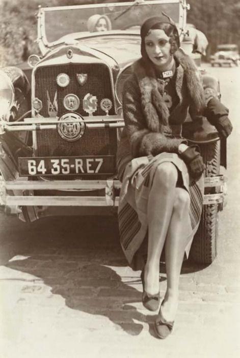"""L'ÉPOQUE ■ Jamais la Mode féminine n'avait connu pareille révolution, en si peu de temps ! Minces, bronzées, les """"garçonnes"""" (titre d'un célèbre roman à scandale), ont coupé courts leurs cheveux et leurs jupes, jeté leurs corsets par dessus les moulins, et roulent à toute vitesse dans leurs bolides décapotables vers les premières stations de ski, ou les plages de la côte d'azur. A Paris, on découvre une musique révolutionnaire"""