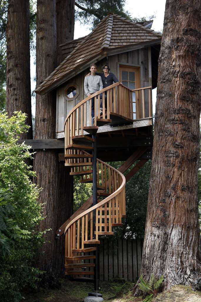 Artist Jay Nelson stands with ceramist Daria Joseph in front of the tree house with a spiral staircase that he built for her in her backyard in Marin County. Photo: Michael Short, The Chronicle