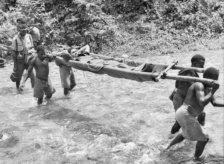 """23 November 1942. Kokoda track. A Wounded Australian soldier being brought in by native bearers affectionately known as """"Fuzzy Wuzzy Angels"""". [Photo: George Silk] [AWM 013641]"""