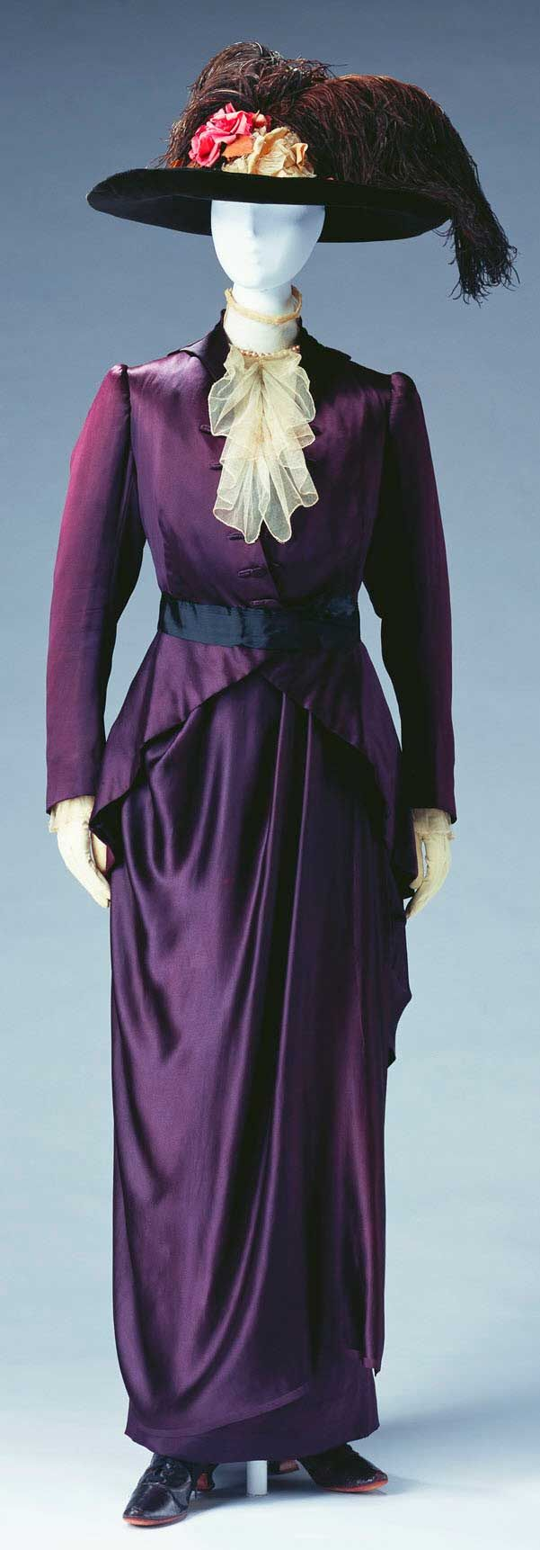 """Pierre Bulloz, Paris, ca. 1910. Deep purple silk satin; set of jacket, bodice, and skirt; black silk faille belt; white cotton tulle jabot on bodice. Kyoto Costume Institute: """"Women started wearing tailored suits, with designs that were influenced by men's clothing, in the middle of the 19th century as traveling wear or sportswear. At around 1910 they became a popular wardrobe staple."""""""