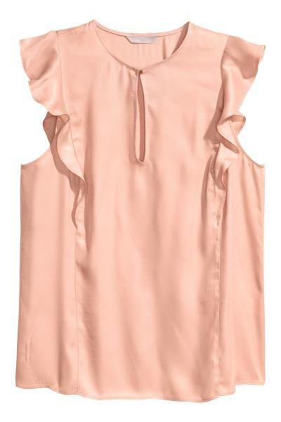 Een mouwloze blouse van satijn met volants voor en achter die doorlopen over de schouders. De blouse heeft een splitje met een knoop voor.