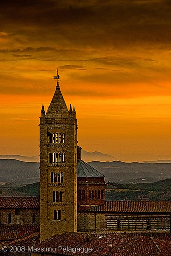 A flaming orange sunset over the stunning hill top medieval city of Massa Marittima Tuscany Italy
