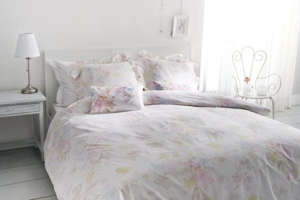 Een dekbedovertek met verfijnde bloemen in pasteltinten, ontworpen ism Beddinghouse