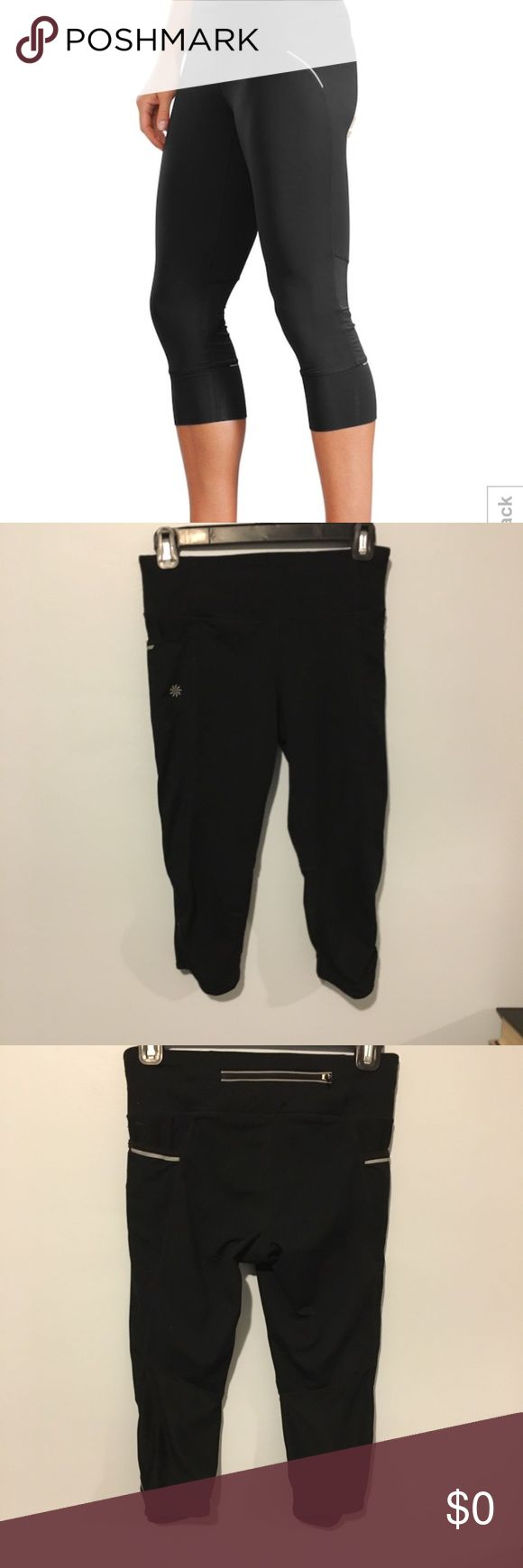 "Athleta Black Workout Capri Leggings Pants XS Cute little pair of workout capris. First photo is stock and slightly differs from actual design on this pair. Back zipper, side mesh panels and reflective strips.  Measurements:  Waist 13.5 Ankle opening 5"" Inseam 14"" Athleta Pants Leggings"