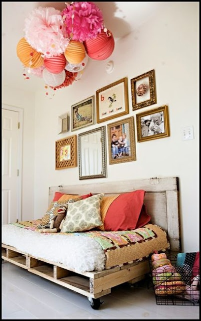 Wood pallets daybed, paper pompoms and paper lanterns.  So adorable!