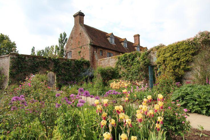 De oude tuinmuren in Sissinghurst kaderen de verschillende tuingedeeltes in. De tuinen zijn onderling verdeeld in diverse thema's. Hier zie je de kleurrijke cottage garden. In bloei zijn de baardirissen (Iris germanica) en sieruien (Allium).