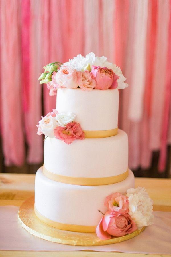 Pretty Flower Adorned Wedding Cake Against a Paper Backdrop   Chloe Luka Photography on @CVBrides via @aislesociety