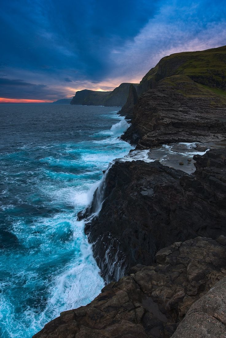 Ocean Spray - Rugged coastline of Island of Vagar on the Faroe Islands with the view of Bøsdalafossur waterfall.