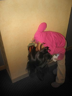 Tooth Fairy door in reception wall of Dentist Dr. Kay Wilson, DDS :: A young patient looks inside :: pic 3 of 3