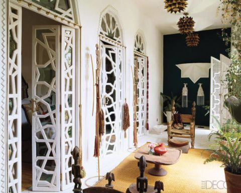 In the master bedroom, the carved-wood chairs are from Mali, the rug is made of reeds, and the wood doors were crafted by local artisans.