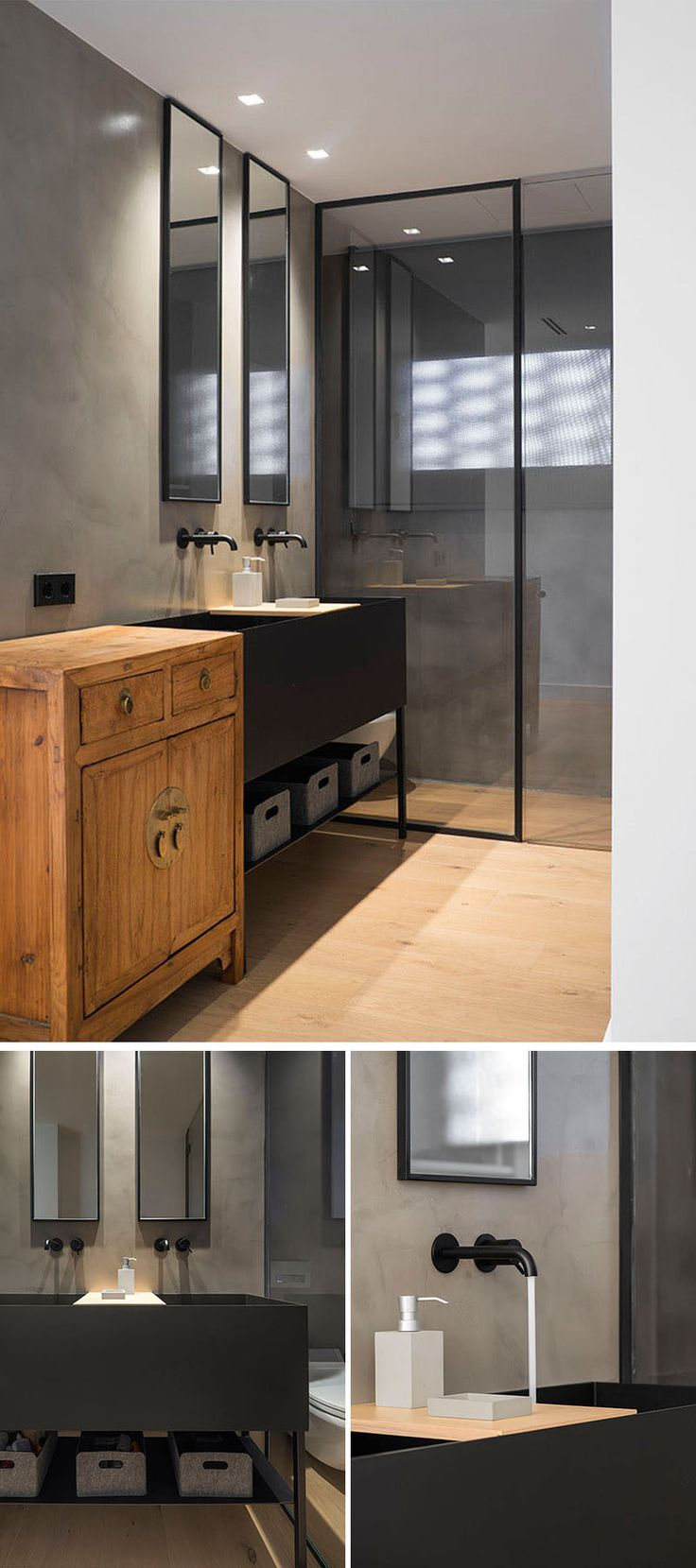 This modern bathroom has a black framed, glass enclosed shower and a vanity area with two rectangular mirrors mounted above the large dual-faucet sink.