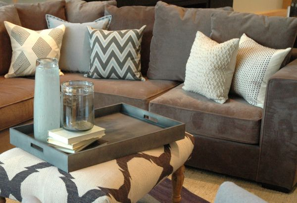 grey suede couch with white and chevron accent pillows, grey and white designed ottoman with grey wood tray.