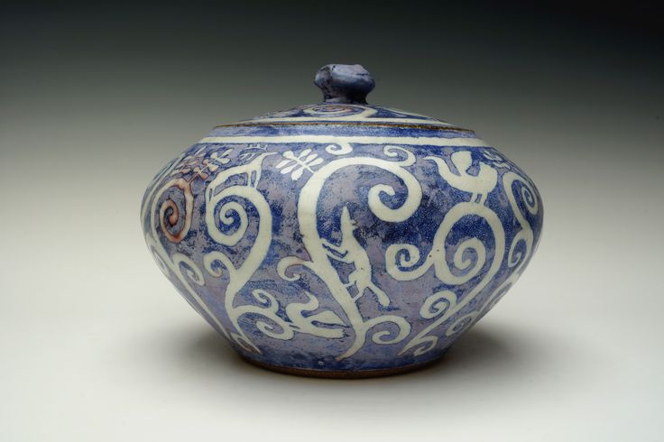 A stoneware casserole with blue glaze over wax resist motif