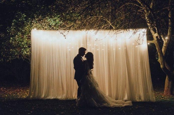 La tendance est au rideau lumineux. Il y a deux types de décoration possible, celle du vrai rideau blanc tout simple et long éclairé par une jolie guirlande de lumières ou de fil verticaux contenant des leds. Pour des clichés romantiques, les mariés peuvent bien sûr posés devant.