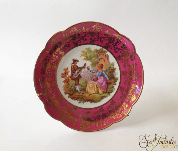 a Medium sized French Limoges china wall plate or charger, Fragonard - romantic themed in ruby and with a gold leaf pattern. Limoges France porcelain wall hanging plate including its holder which allows it to stand or to hang. In excellent condition by SoVintastic, €15,-