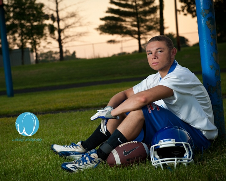 Posing on the field with football gear for senior photo