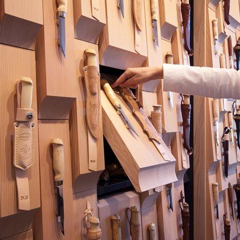 Leather-bound blades displayed against chunky wooden blocksadorn the walls of a Finnish knife shop in Helsinki by designersSuunnittelutoimisto Amerikka
