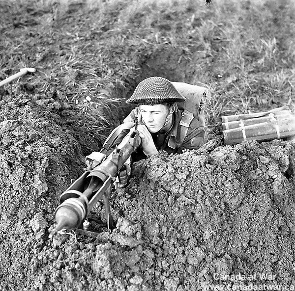 Ortona - Private Edmund Arsenault of The West Nova Scotia Regiment aiming a PIAT anti-tank weapon from a slit trench near Ortona, Italy, 10 January 1944.