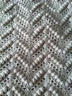 From the website: Tired of the same old multi-color ripple afghan, try this richly textured pattern out for size . It still has the attractive zig-zag pattern, but a popcorn stitch is used to create wonderful texture. Off-white yarn makes an especially rich looking afghan, but any color would work equally well.