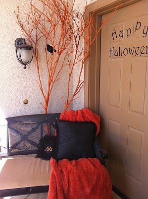 easy and cheap halloween deorating, spray paint a branch and decorate it with cheap black birds or webs