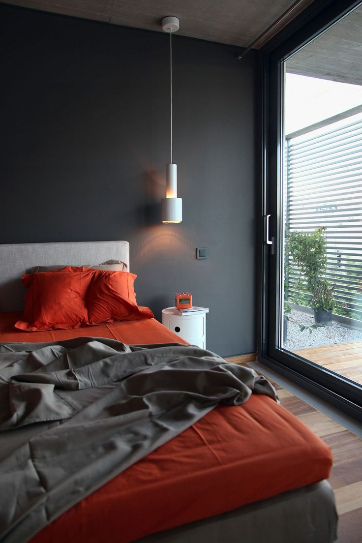 Charcoal bedroom walls, illuminated by an Artek A100 Pendant Lamp.
