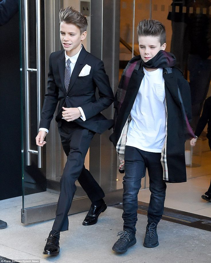 Trendy kids: Model Romeo cut a suave figure in tailoired suit, while young Cruz opted for a plain T-shirt and a distressed pair of black jeans, which was paired with a chic grey scarf and a dark overcoat