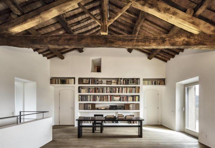 Al primo piano è stato collocato uno spazioso studio open space con libreria disegnata su misura. Le travi originali che corrono lungo il soffitto ricordano il passato antico della struttura