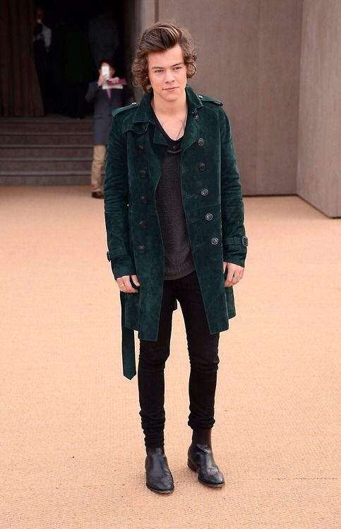 Shop Harry Styles' look for $567:  http://lookastic.com/men/looks/trenchcoat-and-crew-neck-sweater-and-crew-neck-t-shirt-and-jeans-and-chelsea-boots/1235  — Green Trenchcoat  — Charcoal Crew-neck Sweater  — Black Crew-neck T-shirt  — Black Jeans  — Black Leather Chelsea Boots
