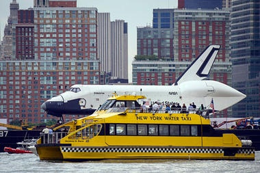 Not something you see everyday!    Riders onboard a New York Water Taxi get a close-up view of the space shuttle Enterprise as it is towed by barge up the Hudson River as it makes the final leg of its journey to its new Manhattan home on the flight deck of the Intrepid Sea, Air & Space Museum, Wednesday.    Bill Ingalls/NASA/AP | http://ow.ly/bqPTd