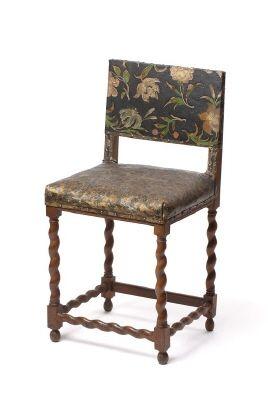 Stol från 1650 cirka gjord av valnöt med spiralsvarvade ben, klädd i gyllenläder med blommor.