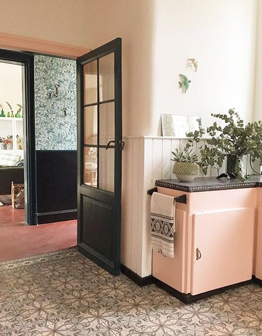Pink kitchen units and black doors. The combination doesn't always work but here it looks fabulous with the patterned tiled floor.