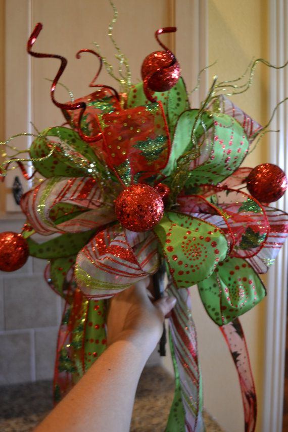 Its almost time to start decorating for christmas! Dress up your tree with a festive tree topper. It has three different ribbons with red glitter balls and green glitter sticks coming out of the top. It measures 14 inches across the top of the bow and 30 inches long. It would work well on a 6 to 7 foot tree.
