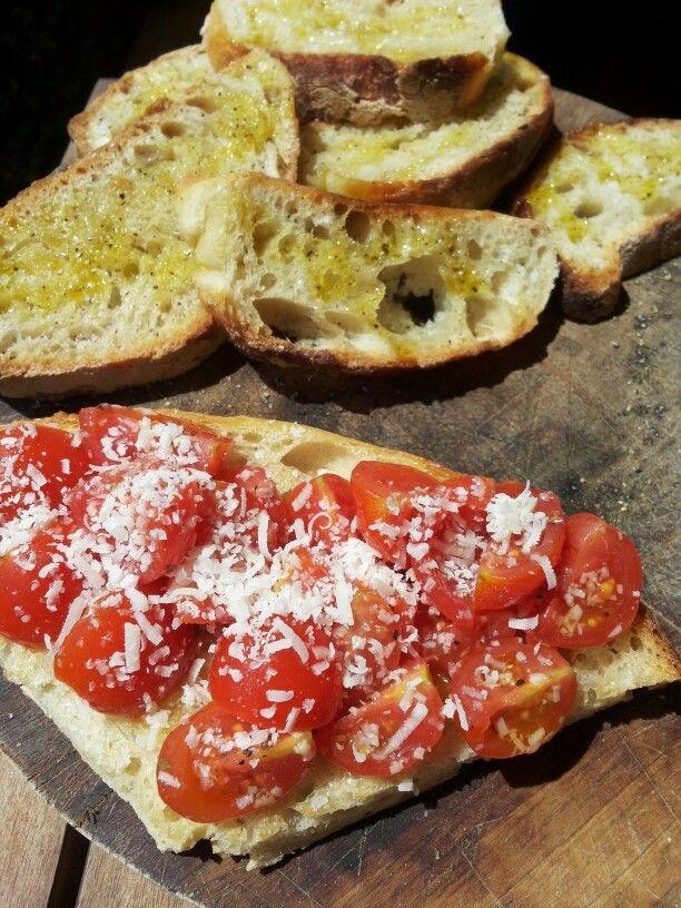 Bruschetta con pomodorini e parmigiano, pane bruscato con olio sale e pepe.  Bruschetta with cherry tomatoes and Parmesan, toasted bread with olive oil salt and pepper.