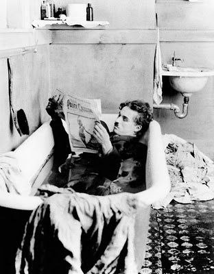 Charlie Chaplin kills three birds with one stone (laundry, bathing, and cultured mind; done, done, and done!).
