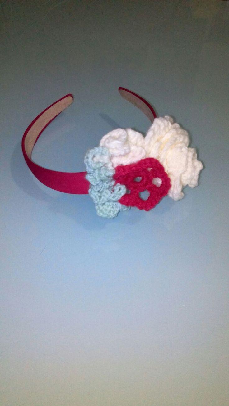 cerchietto per capelli  formato da un fiore rosso foglie verde chiaro e fiore biaco