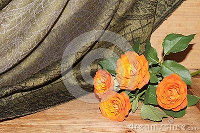 Orange roses on the khaki silk background