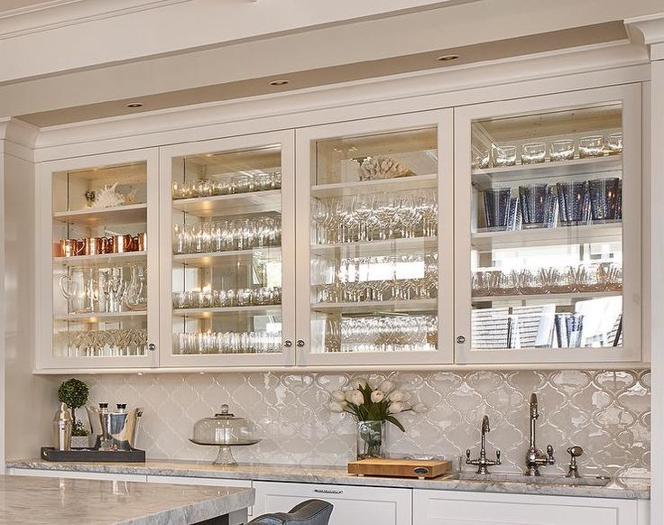 Glam kitchen wet bar boasts glass front upper cabinets over a white glass arabesque tile backsplash and wet bar sink fitted with two dark nickel faucets.