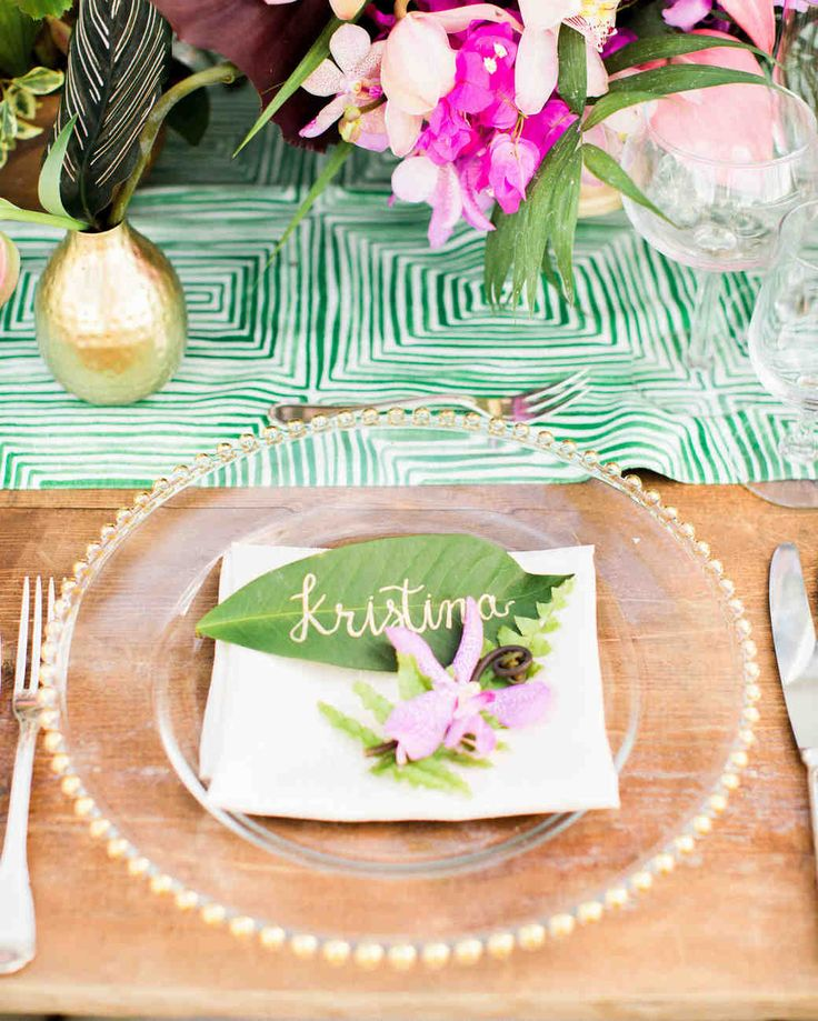 A Casual Beach Wedding in Puako, Hawaii | Martha Stewart Weddings - Patterned green and white runners added color, pattern, and a touch of modernity to the wood tables. The tablescape also featured gold vessels, clear glass chargers with gold beads, and geometric glass terrariums. Guests' names calligraphed on leaves served as place cards. #weddingdecor #weddingideas #seatingcards #weddingflowers