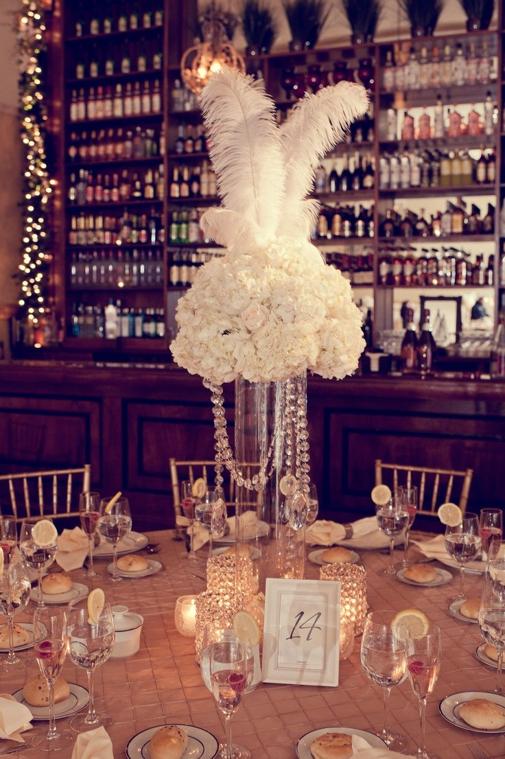 Gatsby-themed floral table centerpiece with tall feathers and crystals