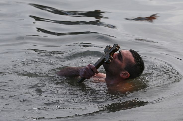 Greek Orthodox faithful Nikolas Solis, 28, a pilgrim from Agrinio of Greece, kisses a wooden crucifix in the Golden Horn in Istanbul, Turkey.