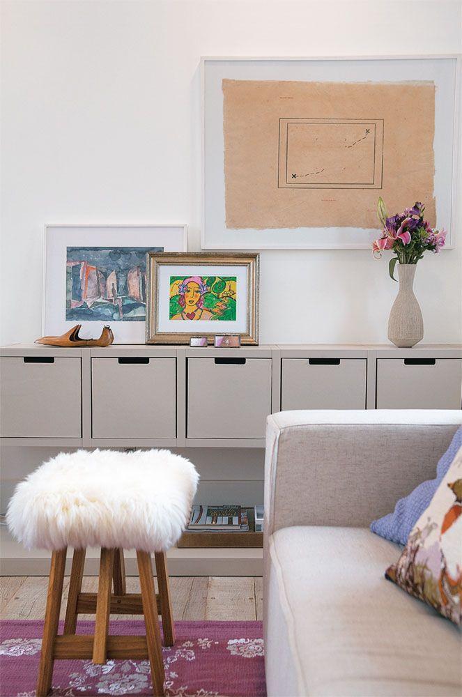 Sobre o móvel baixo, desenhado pela arquiteta e feito pela Ornare, quadro de Isabelle Tuchband e obras de Mônica Filgueiras Eduardo Machado Galeria. A banqueta da Conceito Firma Casa e o tapete da By Kamy agradam ao tato.