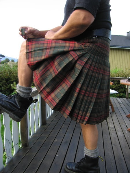 Real men wear a kilt - 1. What is he drinking? 2. Who's downhill from that view?
