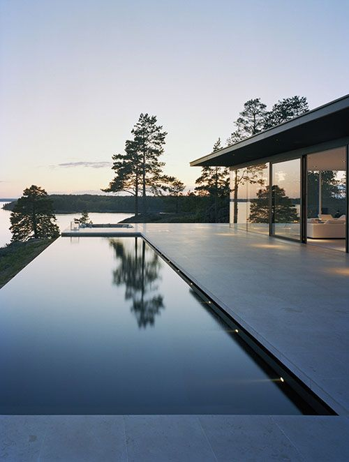 This house on a rocky hilltop in Sweden by Swedish architect John Robert Nilsson sits upon on a limestone-covered concrete plinth, which provides a continuous floor surface inside and outside of the house. The exterior of Villa Överby is finished in matte black, interrupted only by glass walls which provide views out towards the sea.