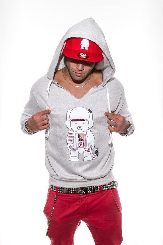 φωτογραφία μόδας, άνδρας ποζάρει φορώντας φούτερ καπέλο και κόκκινο παντελόνι