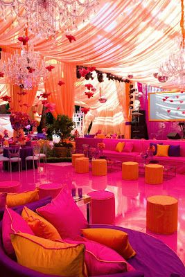 This #reception #tent is decked out with a #bar, couches and crystal #chandeliers. The viberant orange, fuchsia and purple make the space warm and inviting.